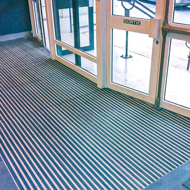 paillassons d'entrés paillassons d'acceuil tapis industriel pose et design. Toutes formes : Circulaire, trapèze, découpe pour poteaux. Structure enroulable ou fermée